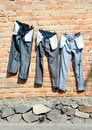 Jeans on clothesline drying clothes line against red brick wall Stock Images