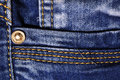 Jeans fabric closeup with seams and metal pin Royalty Free Stock Photos