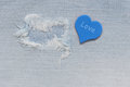 Jeans fabric torn with a blue heart and a word love. Royalty Free Stock Photo