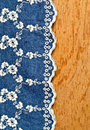 Jeans fabric with white flower embroidery laid over plywood Royalty Free Stock Photo