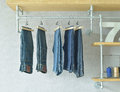 Jeans hanging in industrial style walk in closet at home Royalty Free Stock Photo