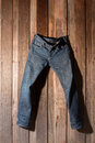Jeans hanging wooden wall Royalty Free Stock Photography