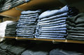 Jeans in a shop many folded on shelves Stock Image