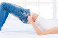 These jeans are too tight cropped image of young blond woman lying on the bed and pulling on Stock Image