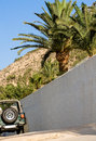 Jeep car parked in the driveway under palm trees Stock Photography