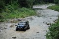 Jeep crossing the river in mountain Stock Image