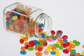 Jelly Beans candy spilled from glass jar on white backg