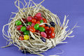 Jelly beans colorful in straw nest on purple background Royalty Free Stock Photo