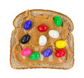Jelly beans on peanut butter on bread a slice of whole wheat with and a white background Royalty Free Stock Photography