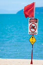 Jelly fish warning sign close up of a jellyfish or marine stinger and red flag at a tropical australian beach Royalty Free Stock Photos