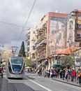 Jerusalem light rail runs along jaffa street with a mural of the on a building in israel Royalty Free Stock Photos