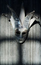 Jester mask hanging on the concrete wall spooky shadows dancing Royalty Free Stock Photo