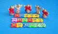 Jesus christ is born message that in white lower case letters on colorful jigsaw shape pieces with an arc of angels on blue Stock Images
