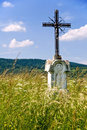 Jesus Christ on old wayside cross in meadow. Stock Images