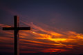 Jesus Christ wooden cross on a background with dramatic, colorful sunset, and orange, purple sky Royalty Free Stock Photo