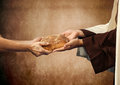 Jesus gives the bread to a beggar on beige background Stock Image