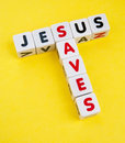 Jesus saves text and with uppercase letters inscribed on small white cubes and arranged crossword style with common letter s Stock Photography
