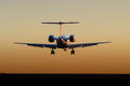 Jet aircraft landing at sunset corporate airliner in silhouette Stock Image