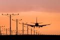 Jet airplane landing bei sonnenuntergang Lizenzfreie Stockbilder