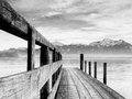 Jetty on lake chiemsee with alps in background and grain effect Royalty Free Stock Image