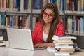 Jeune étudiant using her laptop dans une bibliothèque Image libre de droits