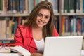 Jeune étudiant using her laptop dans une bibliothèque Photographie stock libre de droits