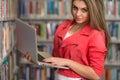 Jeune étudiant using her laptop dans une bibliothèque Photographie stock