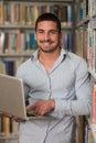 Jeune étudiant using his laptop dans une bibliothèque Photographie stock