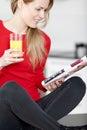 Jeune femme affichant un magazine à la maison Photographie stock libre de droits