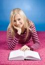Jeune femme blonde se trouvant sur le tapis rose avec le livre Image libre de droits
