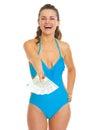 Jeune femme de sourire dans le maillot de bain donnant la fan des euros Image stock