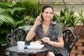 Jeune femme parlant sur un téléphone portable pendant le déjeuner Images stock