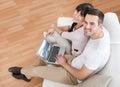 Jeunes couples utilisant l'ordinateur portatif dans le divan Images libres de droits