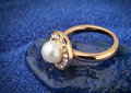 Jewelery ring with pearl on blue sand background