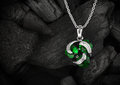 Jewelry pendant witht gem emerald on dark coal background, copys Royalty Free Stock Photo
