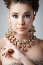 Jewelry young brunette lady with luxury accessories on gray background Royalty Free Stock Image
