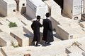 Jewish cemetery orthodox men are walking in the ancient on the mount of olives jerusalem israel Royalty Free Stock Photo