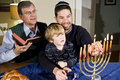 Jewish family lighting Hanukkah menorah Royalty Free Stock Photo
