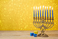 Jewish Hanukkah background with vintage menorah and spinning top dreidel over lights bokeh Royalty Free Stock Photo