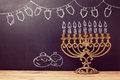 Jewish holiday Hanukkah background with menorah over chalkboard with hand sketched symbols Royalty Free Stock Photo