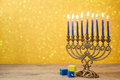 Jewish holiday Hanukkah background with vintage menorah and spinning top dreidel over lights bokeh. Royalty Free Stock Photo