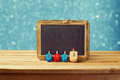 Jewish Holiday Hanukkah background with wooden dreidel spinning top and chalkboard over blue bokeh lights Royalty Free Stock Photo