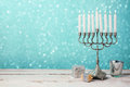 Jewish holiday Hanukkah celebration with menorah, dreidel and gifts on wooden table Royalty Free Stock Photo
