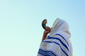Jewish man blowing the Shofar (horn) of Rosh Hashanah (New Year)