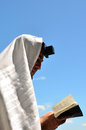 Jewish man pray wearing tallit and tefillin read from the torah book to god under a blue sky on holiday Royalty Free Stock Images