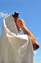 Jewish man pray wearing tallit and tefillin to god under the blue sky on holiday Stock Photography