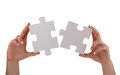 Jigsaw piece solution puzzle pieces joining together concept for unity teamwork or success with blank white face for message Stock Photo