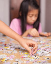 Jigsaw puzzle girl playing on table Royalty Free Stock Photos