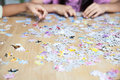 Jigsaw puzzle girl playing on table Royalty Free Stock Photo
