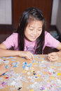 Jigsaw puzzle girl playing on table Royalty Free Stock Image